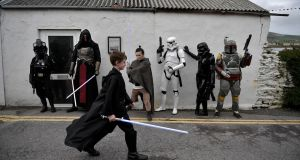 A young Star Wars fan walks past  501st Irish Legion costume players dressed as Star Wars characters in Portmagee Harbour amid the May the Fourth be With You festival  in Portmagee, Ireland. The first ever Star Wars festival is taking place against the backdrop of the famous Skellig Michael island which was used extensively in Episode VII and Episode VIII of the  science fiction saga. Photograph: Charles McQuillan/Getty Images