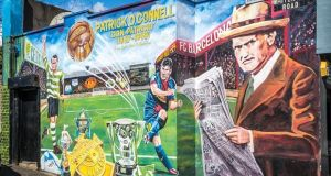 A Celtic and Barcelona mural in West Belfast depicting Patrick O'Connell reading coverage of the start of the Spanish Civil War.