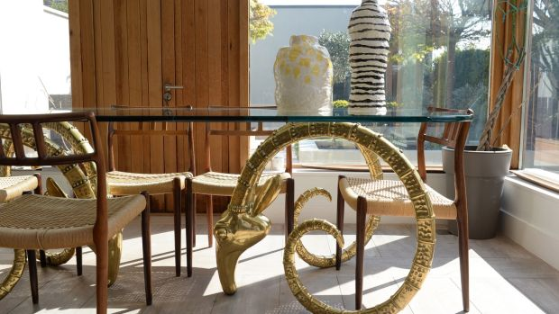 Glass-topped ibex dining table supported by brass rams' heads. Photograph: Dara Mac Dónaill