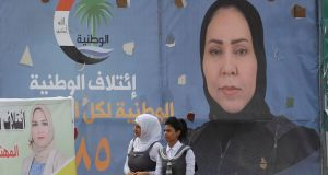 Young women walk past campaign posters of candidates in Tikrit, Iraq, ahead of Saturday's  parliamentary election . Photograph: Khalid al-Mousily/Reuters