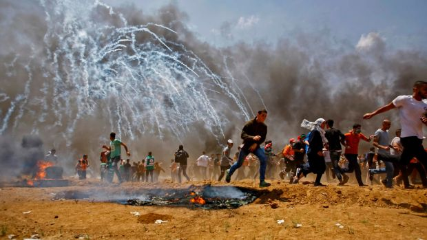 Palestinians run for cover from tear gas during clashes with Israeli security forces near the border between Israel and the Gaza Strip on Monday. Photograph: Mohammed Abed/AFP/Getty Images