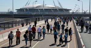 People walk on Sunday on Yahtenny Bridge  near the St Petersburg stadium, which will host matches of the 2018 football World Cup. Photograph: Anton Vaganov/Reuters