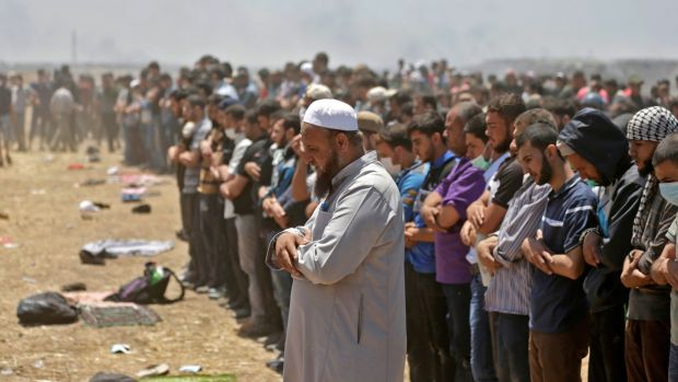 Palestinians pray during clashes with Israeli forces near the border between the Gaza Strip and Israel east of Gaza City on May 14th, during a demonstration on the day of the US embassy move to Jerusalem. Photograph: Mahmud Hams/AFP/Getty