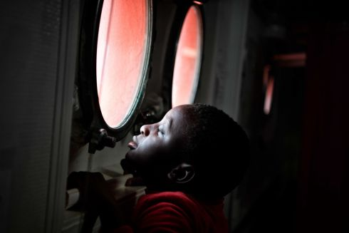 MIGRANT RESCUE: A child seeks to peer out from the porthole of the MV Aquarius upon its arrival at the Sicilian port of Messina. Seventy-three migrants of various nationalities, including women and children, had been rescued in recent days by the rescue vessel, chartered by SOS-Mediterranee and Doctors Without Borders. Photograph: Louisa Gouliamaki/AFP/Getty Images