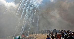 Palestinians run for cover from tear gas fired by Israeli forces near the border between the Gaza strip and Israel east of Gaza City, on Monday. Photograph:  Mahmud Hams/AFP/Getty Images