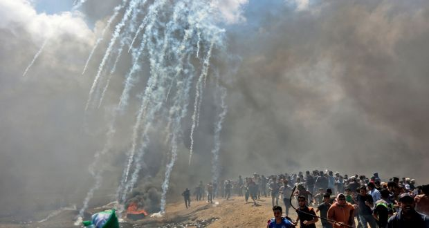 90fe73855d43 Palestinians run for cover from tear gas fired by Israeli forces near the  border between the