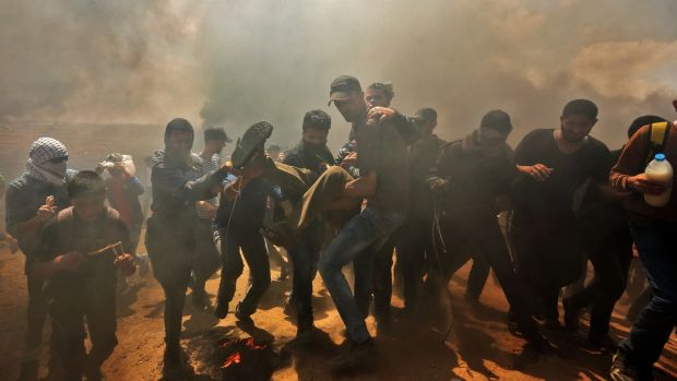 Palestinians carry a demonstrator injured during clashes with Israeli forces near the border between the Gaza Strip and Israel, east of Gaza City, on Monday. Scores were killed. Photograph: Mahmud Hams/AFP/Getty Images