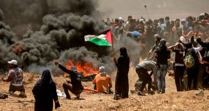 A Palestinian woman holding her national flag looks at clashes with Israeli forces near the border between the Gaza strip and Israel east of Gaza City. Photograph: Getty Images