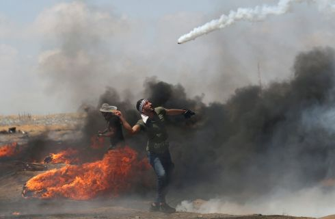 A demonstrator uses a racket to return a tear gas canister fired by Israeli troops, May 11th, 2018. Photograph: REUTERS/Ibraheem Abu Mustafa