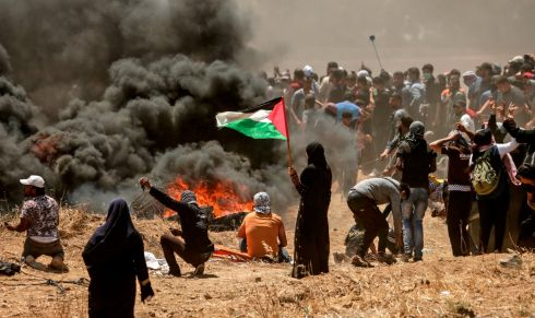 A Palestinian woman holding her national flag looks at clashes with Israeli forces near the border between the Gaza strip and Israel east of Gaza City on May 14th, 2018.  Photograph: Mahmud Hams/AFP/Getty Images