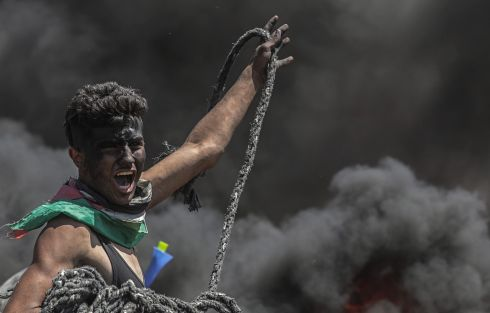 A Palestinian protester holds a rope during violent clashes with Israeli forces.  Photograph: Mohammed Saber/ EPA