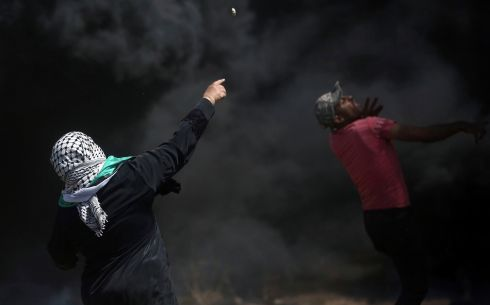 Palestinian protesters hurl stones at Israeli troops. Photograph: AP Photo/Khalil Hamra