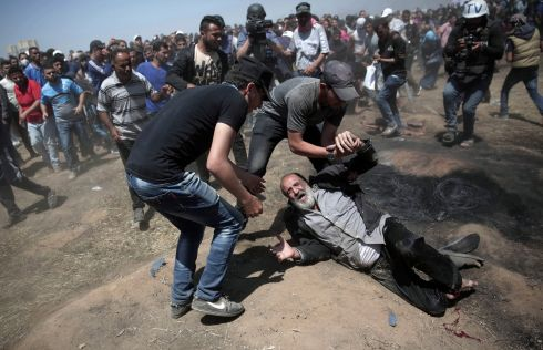 An elderly Palestinian man falls on the ground after being shot by Israeli troops. Photograph: AP Photo/Adel Hana