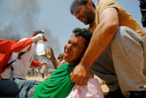 A Palestinian man assists a wounded protestor. Photograph: Mahmud Hams/AFP/Getty Images