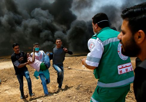 Palestinians carry a wounded protestor during clashes with Israeli security forces near the border between Israel and the Gaza Strip, east of Jabalia on May 14, 2018. Photograph: Mahmud Hams/AFP/Getty Images