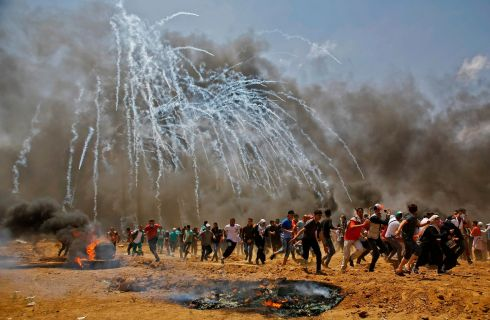 Demonstrators run for cover from tear gas. Photograph: Mahmud Hams/AFP/Getty Images