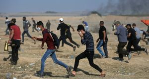 Palestinian protesters run for cover from teargas fired by Israeli troops during a protest at the Gaza Strip's border with Israel on Tuesday. Photograph: Khalil Hamra/PA