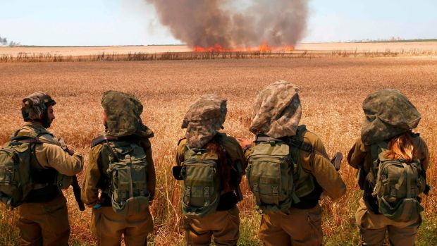 Israeli soldiers walk watch smoke from a fire in a wheat field near the Kibbutz of Nahal Oz in Israel, along the border with the Gaza Strip on Monday. Photograph: Jack Guez/AFP/Getty Images