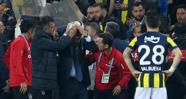 9a4400e6 Besiktas manager Senol Gunes holds his head after being hit by a missile  during a Turkish