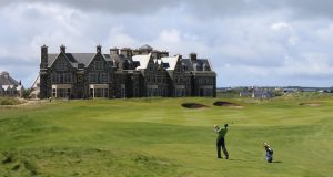 A golfer plies his trade on  the Doonbeg Golf Links course in front of the resort hotel, in Doonbeg, Co Clare. The resort is owned by US president Donald Trump. File photograph: Niall Carson/PA Wire
