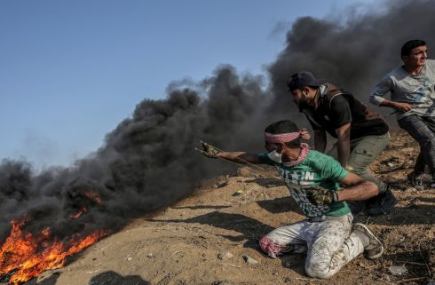 GAZA STRIP: A Palestinian protester fires stones during clashes near the border with Israel in the east of Gaza Strip. According to Palestinian medical sources, two Palestinian protesters were shot dead by the Israeli army on Tuesday in Gaza. Photograph: Mohammed Saber/EPA