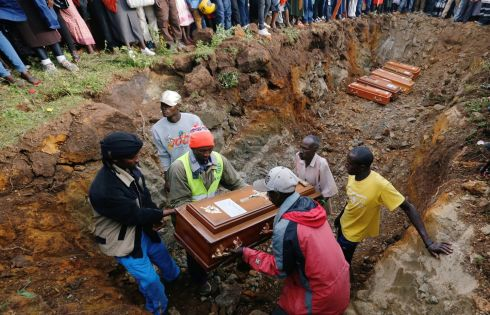 KENYAN FLOOD: Relatives arrange the coffins of their kin inside a mass grave during the burial of people killed when a dam burst its walls, overrunning nearby homes, in Solai town near Nakuru, Kenya. Photograph: Thomas Mukoya/Reuters
