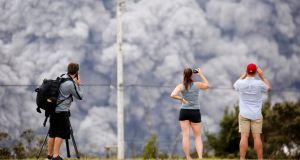 People watch as ash erupt from the Halemaumau crater near the community of Volcano during ongoing eruptions of the Kilauea Volcano in Hawaii, on Wednesday. Photograph:Terray Sylvester/Reuters