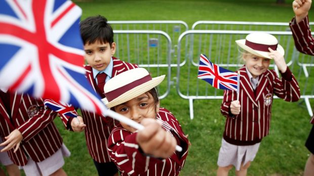 School children in uniform wave Union Flags outside Windsor Castle ahead of Prince Harry and Meghan Markle's wedding, in Windsor. Photograph: Damir Sagolj/Reuters