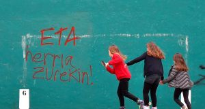 "Girls skate next to a graffiti reading in Basque ""ETA, the people with you"" in the Spanish Basque village of Hernani. The militant separatist group announced its dissolution earlier this month. Photograph: Ander Gillenea/AFP/Getty Images"