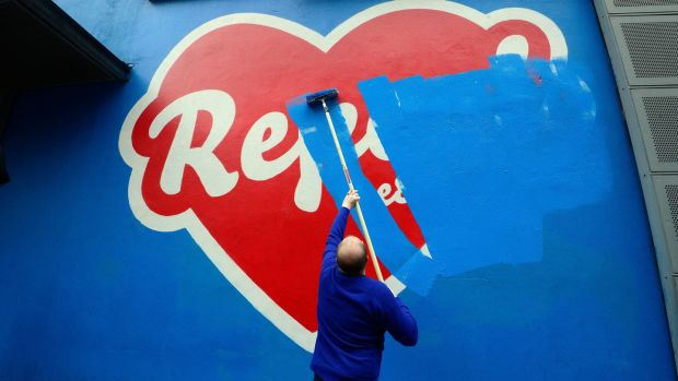 Cian O'Brien, artistic director of the Project Theatre, painting over the Repeal art work by artist Maser. Photograph: Cyril Byrne / The Irish Times