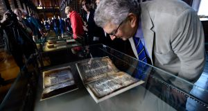 Prof Damian Mc Manus reading a copy of a 14th century Brehon manuscript in the Long Room of Trinity College. Photograph: Cyril Byrne/The Irish Times
