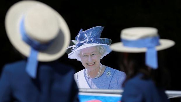 Schoolgirls walk past a cardboard cutout of Queen Elizabeth near Windsor Castle, on Friday. Photograph: Marko Djurica/Reuters