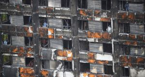 File photograph: Workers stand inside the burnt out remains of the Grenfell tower in London, Britain, where 72 people died. Photograph: Reuters/Hannah Mckay