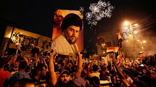 Supporters of Shia cleric Muqtada al-Sadr carry his image as they celebrate in Tahrir Square, Baghdad last Sunday. Photograph: Hadi Mizban/AP