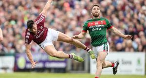 Survival of the fittest: Mayo's Chris Barrett  and Galway's Damien Comer at MacHale Park. Photograph: Cathal Noonan/Inpho