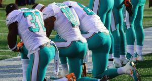 Miami Dolphins players kneel during the National Anthem before their game against the New England Patriots last November. Photograph: PA