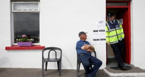 Garda Pat Mcllroy chats to  Jimmy Sweeney as he waits to cast his vote in the referendum on the Eighth Amendment, on Gola Island. Photograph: Reuters