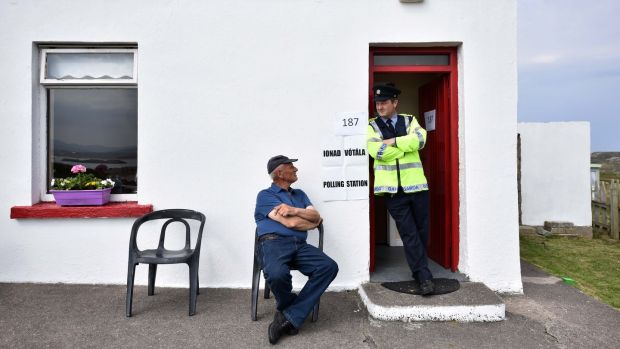 Garda Pat McElroy chats with resident Jimmy Sweeney whose house acts as the polling station on Gola Island. Photograph: Charles McQuillan/Getty Images