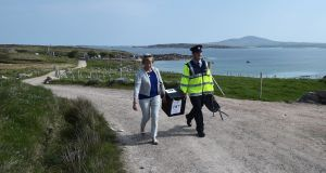 Garda  Pat McElroy helps presiding officer Nancy Sharkey carry a ballot box as they walk to the local polling station  in Gola Island, off Donegal, on Thursday. Photograph:  Charles McQuillan/Getty Images