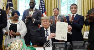 US president Donald Trump holds a signed pardon for boxer Jack Johnson in the Oval Office of the White House in Washington, DC. Photograph: Olivier Douliery-Pool/Getty Images
