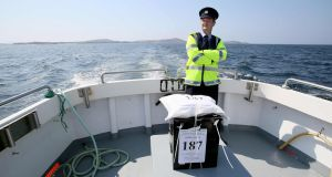 Garda officer Pat McElroy stands with the sealed ballot box as he travels back to the mainland from Gola Island, off the Donegal coast, one of 12 island communities voting on Thursday in the referendum on whether to repeal the Eighth Amendment. Photograph: Paul Faith/AFP/Getty Images