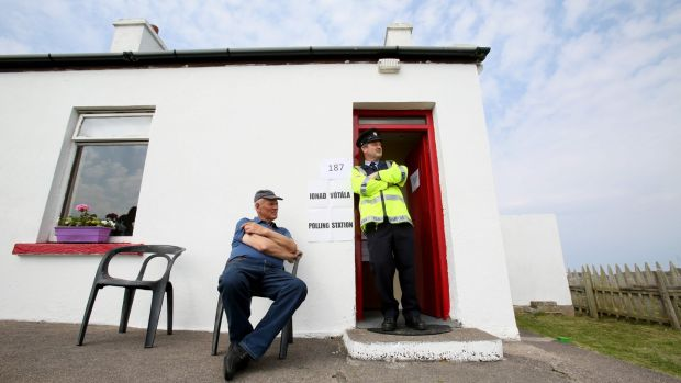 Garda Pat McElroy chats with Jimmy Sweeney (left) whose home acted as a temporary polling station on Gola Island, off the Donegal coast. Photograph: Paul Faith/AFP/Getty Images