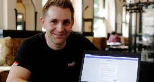 Austrian lawyer and privacy activist Max Schrems displays his Facebook account's updated terms page.  Photograph: Heinz-Peter Bader/Reuters
