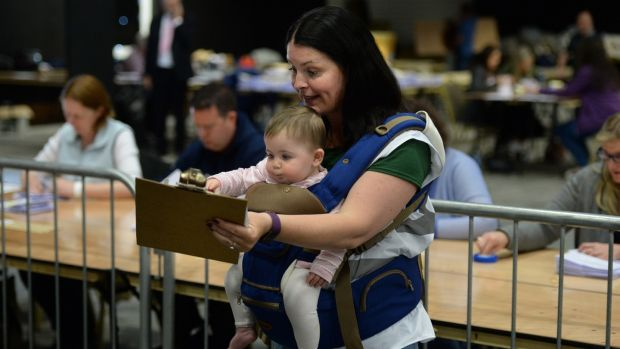 Vivienne Knight Hughes, from Balbriggan, keeping tally with baby Méabh Hughes at the Dublin county referendum count centre in Citywest, Dublin. Photograph: Dara Mac Dónaill/The Irish Times