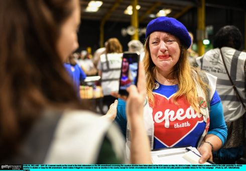 A woman reacts at the RDS as early tallies reflect an Irish Times exit poll predicting a landslide victory for repeal. Photograph: Jeff J Mitchell/Getty Images