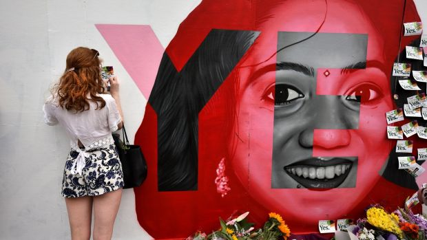 A woman writes a note on the Savita Halappanavar mural in Portabello, Dublin on Saturday. Photograph: Charles McQuillan/Getty