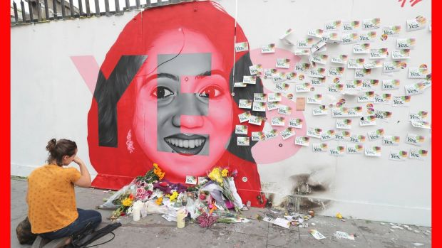 A woman kneels in front of a mural of Savita Halappanavar in Dublin. Photograph: Niall Carson/PA