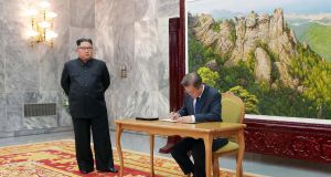 South Korea's president Moon Jae-in  signs a guestbook as North Korea's leader Kim Jong Un looks on during their second summit at the north side of the truce village of Panmunjom in the Demilitarized Zone (DMZ). Photograph:  KCNA via  KNS/AFP/Getty