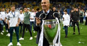 Real Madrid's French coach Zinedine Zidane gestures the number three and holds the trophy as he celebrates winning the UEFA Champions League final football match between Liverpool and Real Madrid at the Olympic Stadium in Kiev, Ukraine. Photograph: Franck Fife/AFP/Getty