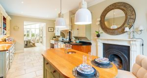 The kitchen is smart, with a timber-topped island unit, marble fireplace, cream Aga and cream kitchen units.